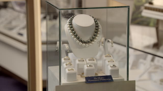 "CLOSE ANGLE OF  GLASS JEWELRY CASE WITH DIAMOND RINGS, PEARL NECKLACE, PEARL EARRINGS, AND SIGN READING ""NA HOKU HAWAIIAN HEIRLOOM."" CAMERA PANS RIGHT TO LEFT TO ADDITIONAL JEWELRY CASES WITH DIAMOND RINGS AND SIGNS READING ""NA HOKU SOLITAIRE."" COULD BE J"