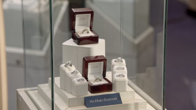 """close angle of  glass jewelry case with diamond rings, pearl necklace, pearl earrings, and sign reading """"na hoku hawaiian heirloom."""" camera pans right to left to additional jewelry cases with diamond rings and signs reading """"na hoku solitaire."""" could be j - jewellery stock videos & royalty-free footage"""