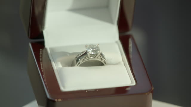 close angle of diamond ring in glass display or jewelry case. could be jewelry store. ring sits in small box or case. engagement or wedding ring. - jewelry box stock videos and b-roll footage