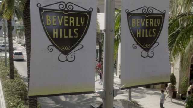 vídeos de stock, filmes e b-roll de close angle of sign for beverly hills in fg. high angle down of rodeo drive in bg. pedestrians visible walking around upper class shopping area in bg. cars driving on city street. - beverly hills