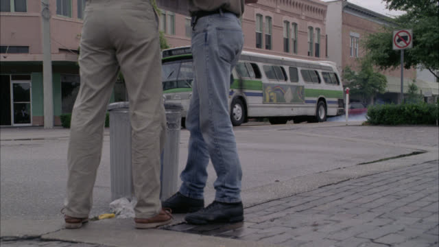 medium angle, low shot of two men, seen from waist down, appear to be talking as city bus starts driving off, turns toward two men and attempts to run them over, knocking into trash can. the two men run frantically out of the way in nick of time. other pe - bulevar stock-videos und b-roll-filmmaterial
