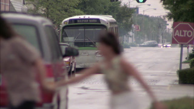 stockvideo's en b-roll-footage met wide angle of city bus weaving in and out of traffic, almost hitting cars in its path. as bus comes to stop, there appears to be no driver at the wheel. mysterious, stunts. people, pedestrians seen crossing road in hurry or panic. bus route displays '1 bu - bulevar