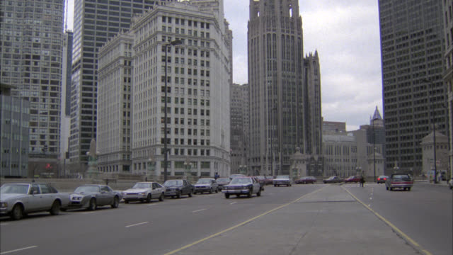 wide angle, pan right to left of white cadillac convertible car driving through chicago business district or downtown city streets. chicago tribune building, office buildings visible in bg. flashing siren indicates could be undercover police car. skyscrap - michigan avenue bridge stock videos and b-roll footage