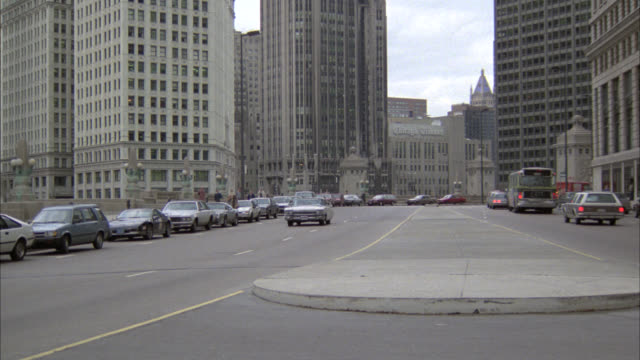 wide angle of white cadillac convertible car driving through chicago business district or downtown city streets. chicago tribune building, office buildings visible in bg. flashing siren indicates could be undercover police car. skyscrapers and high rise o - michigan avenue bridge stock videos and b-roll footage
