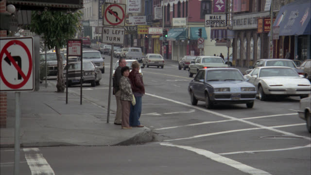 wide angle tracking shot of cadillac racing through city streets in san francisco. strip clubs, storefronts, pedestrians and traffic visible. apartments, row houses, cars, cadillac seems to be following another car. reckless driving. could be car chase. - 1985年点の映像素材/bロール