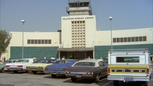 wide angle of burbank airport. parking lot with cars and ford pickup truck parked in front of terminal. control tower and people walking near entrance. blue skies. - burbank stock-videos und b-roll-filmmaterial