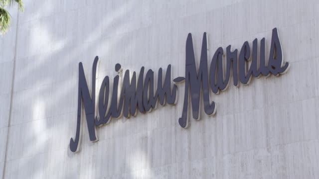zoom in on sign for neiman-marcus on wilshire boulevard in beverly hills. upper class shopping area. upper class department store. palm trees in fg. - neiman marcus stock videos & royalty-free footage