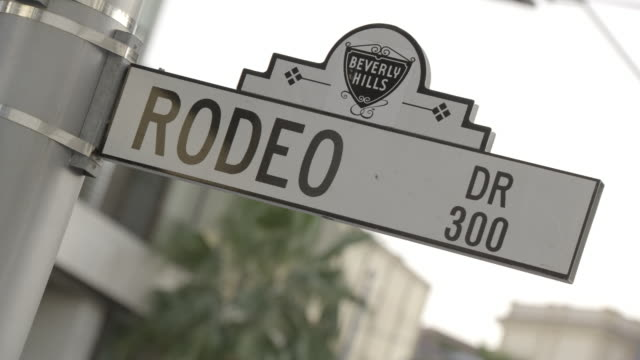 zoom in on rodeo drive street sign in beverly hills. upper class shopping area. - beverly hills stock-videos und b-roll-filmmaterial
