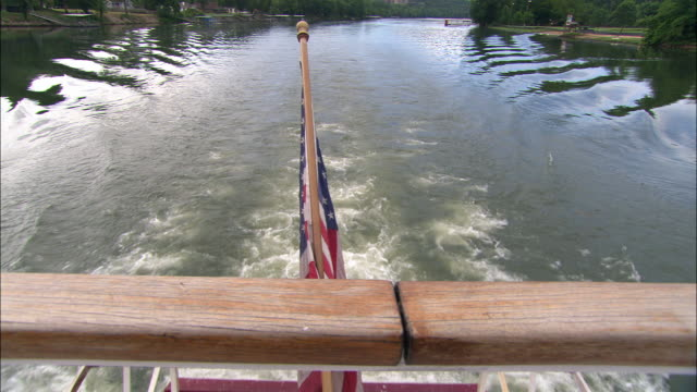 tracking shot, straight back of paddlewheeler boat. camera moves slightly up from paddle wheels to reveal calm, serene, scenic view of mountains, river banks, rippling water, and blue skies. american flag visible in fg. could be riverboat tour. - ミズーリ州点の映像素材/bロール