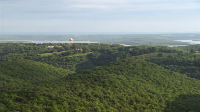 pan left to right, right to left wide angle of branson, missouri. mountains, water towers, trees, lakes or rivers visible over panoramic views.  small highway with cars driving at left in small town. partly cloudy day with blue skies. picturesque. - missouri stock videos & royalty-free footage