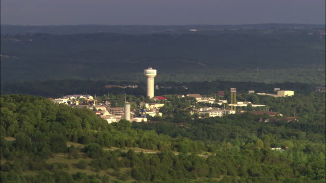 pull back of mountainous, rural area of branson, missouri. camera pans right to left. mountains, water towers, trees, visible over panoramic views.  small houses and highway with cars driving visible in far bg. picturesque. partly sunny skies. - missouri mellanvästern bildbanksvideor och videomaterial från bakom kulisserna