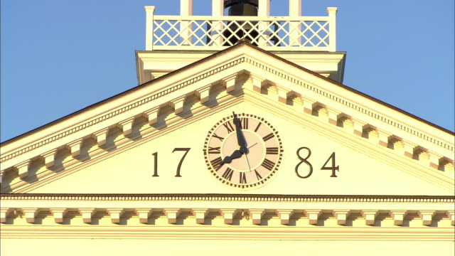 vídeos de stock e filmes b-roll de zoom in on clock tower of dartmouth hall of dartmouth college campus. trees, chimneys, lawn, blue skies visible. camera pulls back, zooms in again. could be sunrise if clock is broken. ivy league. - dartmouth