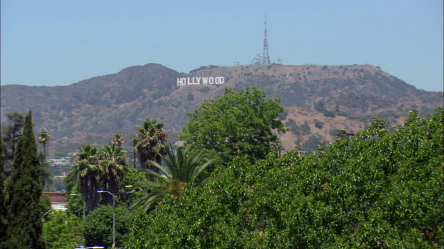 wide angle of hollywood sign, located on southern slope of mount lee in hollywood, california. radio tower at right. palm trees in fg. clear blue skies. - wide stock videos & royalty-free footage