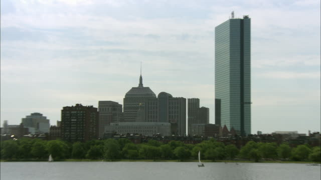 wide angle pull back of boston skyline. john hancock place, prudential tower and berkeley building visible in bg. skyscrapers, office buildings. zoom in on charles river with sailboats, rowboats, motorboat, buoys, rippling calm water. sunny, partly cloudy - back bay boston stock videos & royalty-free footage