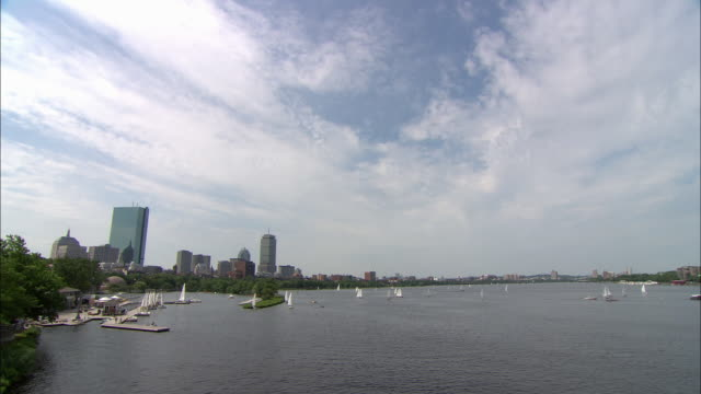pull back, wide angle of boston skyline near small marina with sailboats on charles river. zoom in and out to view john hancock place, prudential tower and berkeley building visible in bg. rippling calm water. sunny, partly cloudy skies. small bridge visi - back bay stock-videos und b-roll-filmmaterial