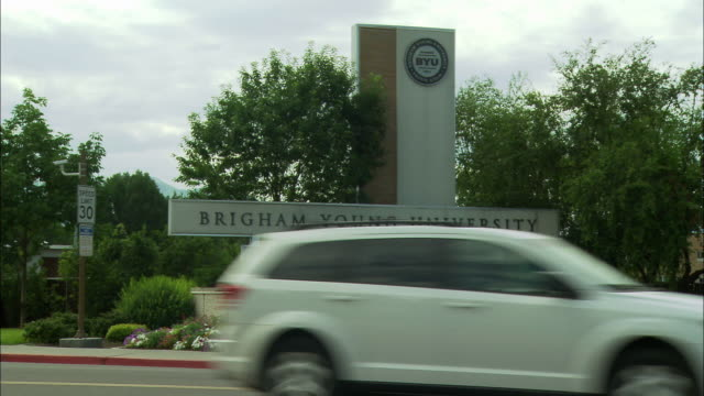 "wide angle of brigham young university sign, provo, utah. trees, flowers surround sign that reads, ""the world is our campus."" pickup truck and cars driving in fg. pans left to right. - provo点の映像素材/bロール"