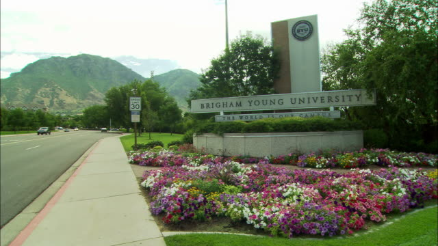 "wide angle of brigham young university sign, provo, utah. trees, flowers surround sign that reads, ""the world is our campus."" cars driving along road at left. mountains in bg. - provo stock videos & royalty-free footage"