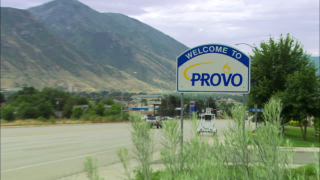 "zoom in on sign, ""welcome to provo"" along small highway in city of provo, utah. mountains at left, chevron gas station, american flag, trees, weeds, visible. suv drives by. could be small town, rural areas. - provo点の映像素材/bロール"