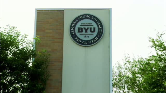"vidéos et rushes de close angle to wide angle of brigham young university sign, provo, utah. trees, flowers surround sign that reads, ""the world is our campus."" mountains in bg. - provo"