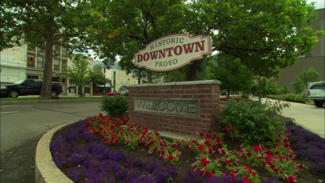 """wide angle of sign, """"historic downtown provo."""" flowers surround welcome sign. provo utah. trees, storefronts, street visible. cars drive by. - provo stock videos & royalty-free footage"""
