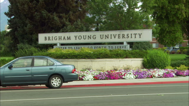 """wide angle of brigham young university sign, provo, utah. trees, flowers surround sign that reads, """"enter to learn, go forth to serve."""" cars drive in fg, pan left to pedestrians or students walking across street on crosswalk. tire shop at left. child and - provo stock videos & royalty-free footage"""