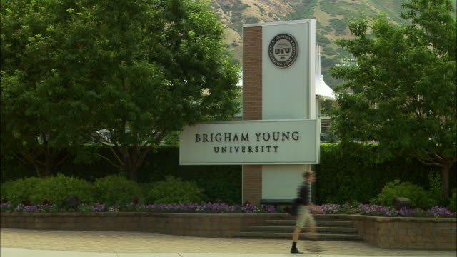 vídeos de stock e filmes b-roll de wide angle of brigham young university sign, provo, utah. trees, flowers surround sign. pedestrian or student wearing shorts walks left to right in fg. cars, trucks, drive by. mountains in bg. college campuses. universities. - provo