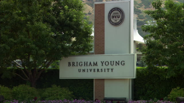 pan down to brigham young university sign, provo, utah. trees, flowers surround sign. pull back from sign, zoom in on mountainous backdrop. college campuses. - provo stock-videos und b-roll-filmmaterial