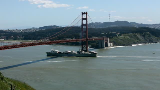 wide angle of golden gate bridge. ship or freighter going under bridge. hills in bg. san francisco bay. landmark. - golden gate bridge stock videos & royalty-free footage
