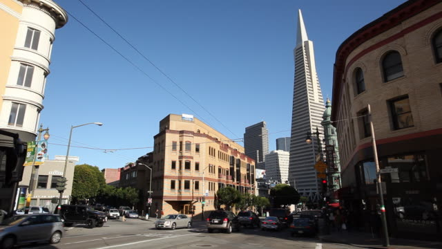 wide angle of cars on city streets. pacific and kearny. north beach. multi-story brick office or apartment buildings. skyscrapers and transamerica pyramid in bg. - north pacific stock videos & royalty-free footage