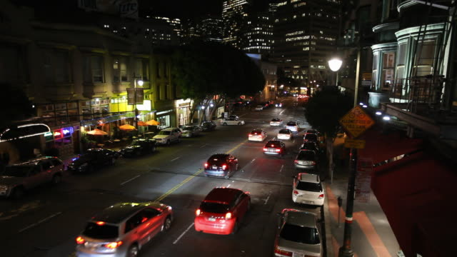 vidéos et rushes de wide angle of cars driving on columbus st. toward transamerica pyramid and other high rise office buildings, skycrapers in downtown san francisco or financial district. columbus tower or sentinel building. - transamerica pyramid san francisco