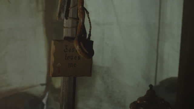"pan up of snake on ""jesus loves me"" sign on wooden post, cross. - 2013年点の映像素材/bロール"