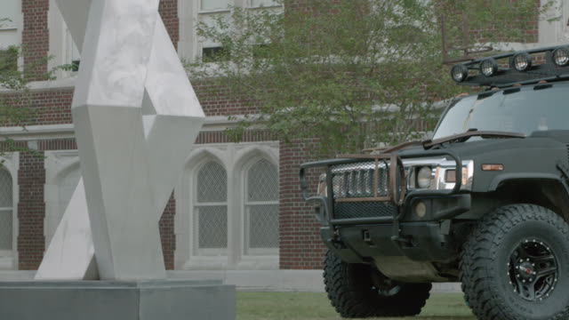 pan right to left of suv, hummer, driving through college campus, crashing into sculpture in sculpture garden. loyola university. car stunt. could be part of car chase. - hummer stock videos and b-roll footage