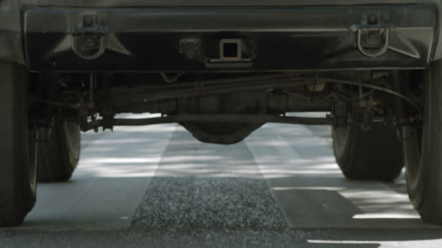 medium angle moving pov of hummer or suv, wheels and bumper, driving on street. - hummer stock videos and b-roll footage