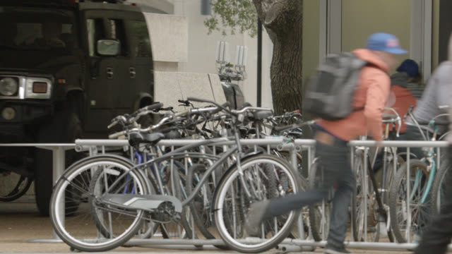 pan left to right as hummer or suv, college campus, crashes into bicycle racks. could be part of car chase. students run out of the way. panic. near collision. stunts. accidents, collisions. - crash stock videos & royalty-free footage