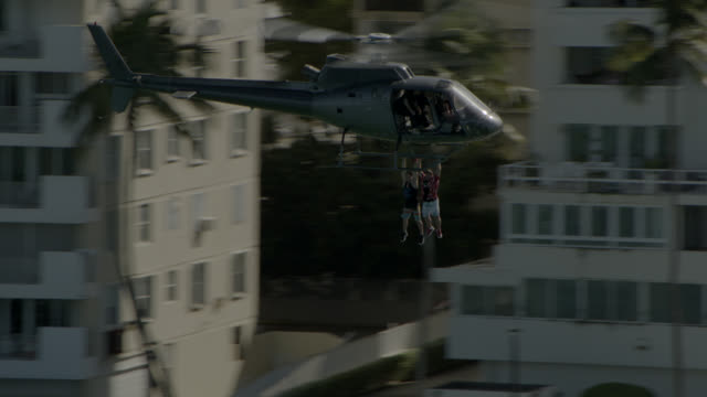 aerial of helicopter with two men hanging on. flying over ocean and beach. high rise beachfront hotels or apartment buildings. stunts. - stunt stock videos & royalty-free footage