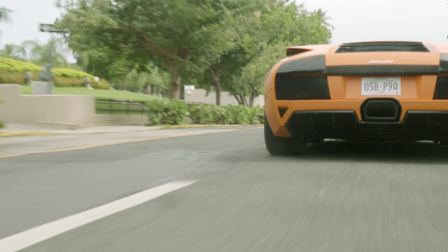 tracking shot of lamborghini, luxury sports car, driving on city street, swerving between cars. could be part of car chase. car stunt. - sports car stock videos & royalty-free footage