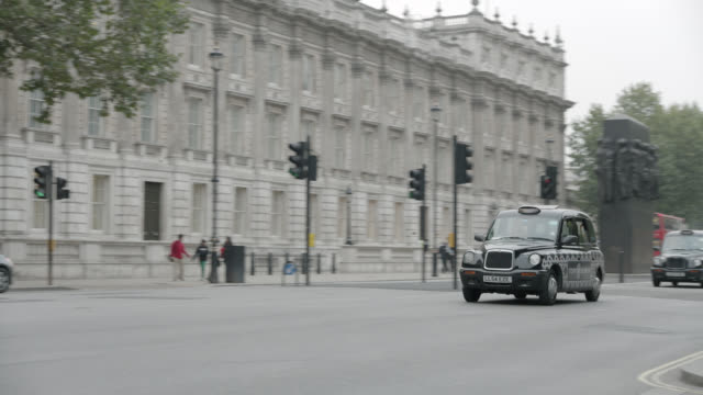 pan right to left of taxi driving city street near entrance to 10 downing street and government buildings. whitehall sw1. pedestrians and tourists visible. women of world war ii monumnet or memorial visible. - 10 downing street stock videos and b-roll footage