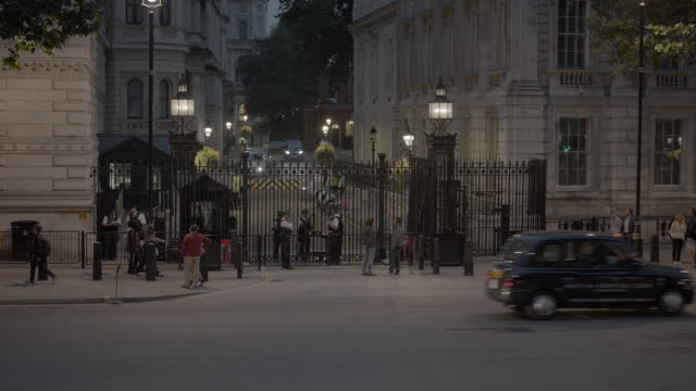 medium angle of entrance to 10 downing street and government buildings. whitehall sw1. pedestrians and tourists visible. cars, taxis, and double deck buses visible on city street. - downing street stock videos and b-roll footage