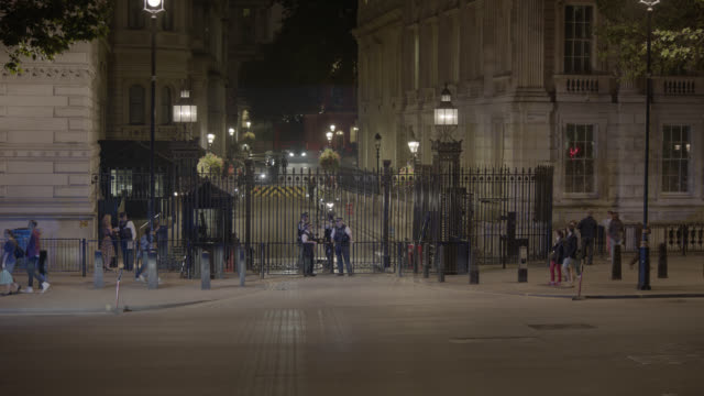 medium angle of entrance to 10 downing street and government buildings. whitehall sw1. pedestrians and tourists visible. cars, taxis, and double deck buses visible on city street. - 10 downing street stock videos and b-roll footage