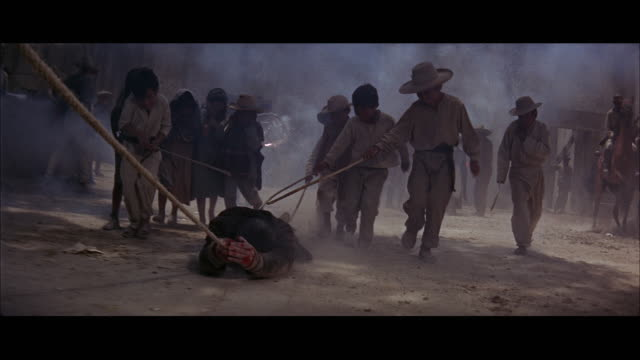 MEDIUM CLOSE UP - MOVING SHOT - MAN IS DRAGGED THROUGH STREET - LAUGHING MEXICAN SPECTATORS.