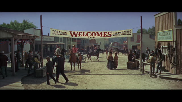 "OLD WESTERN STREET - PEOPLE, HORSE RIDERS, WAGONS - SHOW ALARM AND START TO EXIT - BANNER: ""BORACHO WELCOMES THE GREAT RACERS."""