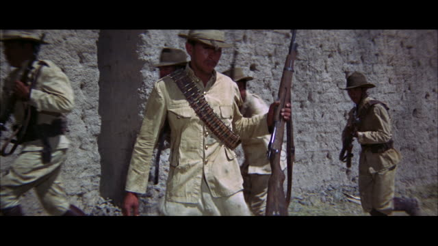 CLOSE UP - THREE ARMED MEXICAN SOLDIERS BY WALL - ARE SHOT DOWN.