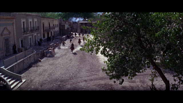 high shot - length of street - people running - riders in fast from background, exiting under camera - one is shot down.  negative cut 804-806. - movie set stock videos and b-roll footage