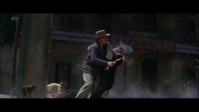vidéos et rushes de close up - man is shot in front of hotel. - format vignette