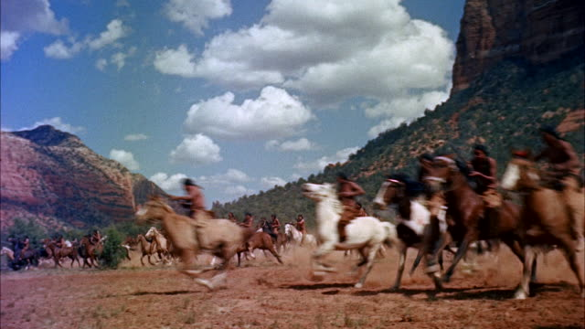 vídeos de stock, filmes e b-roll de long line of indians at foot of a steep rocky butte - all charge to and past camera close.  some shot from horses. - moving past