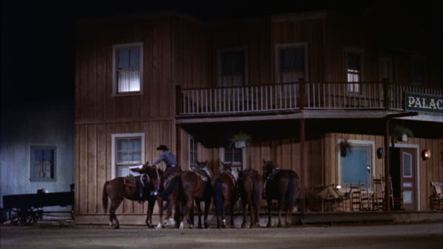 EXTREME LONG SHOT OVER ROLLING GRASSY HILLS TO FOUR HORSE STAGECOACH AT STATION. AT END IT PULLS OUT TOWARD RIGHT.