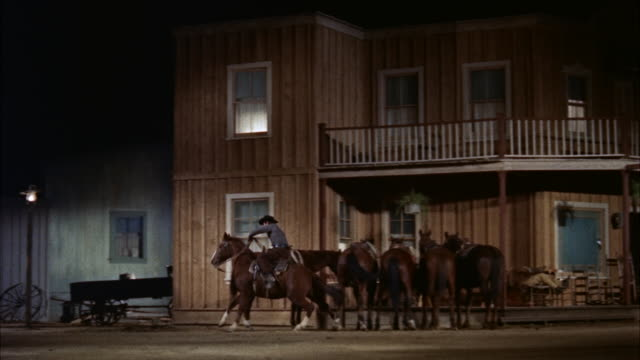 POINT OF VIEW PAST RESTAURANT TO PART OF HOTEL. MAN MOUNTS HORSE AT HOTEL AND TRIES FRANTICALLY TO FIND EXIT FROM TOWN, BUT IS BLOCKED BY GUNMEN. HE RIDES FAST TO AND BY CAMERA AT END. IN FIRST TAKE HE IS SHOT OFF AND HORSE TAKES BAD FALL IN CLOSE FOREGRO