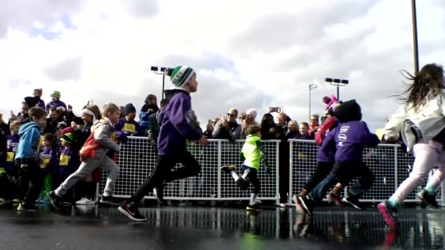 hundreds of children run 100 yards in festive and fun event go past camera - salmini stock videos and b-roll footage