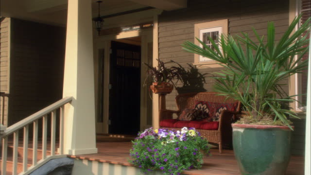 medium angle of upper or middle class porch to shingle style house. white pillar or column at stairs. plants and flowers decorate porch. small sofa or love seat. front door open. - front porch stock videos and b-roll footage