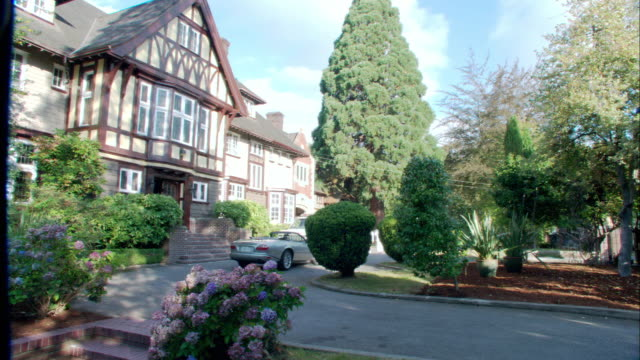 wide angle of tudor style two story house. circular driveway decorated with garden and bushes. could be hedges. upper class. hydrangea flowers. convertible car parked in driveway. could be mansion. - stately home stock videos and b-roll footage